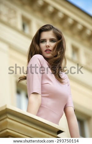 stunning brunette woman on balcony of old palace with long natural hair. stylish make-up and elegant pink dress looking beyond  - stock photo