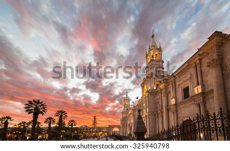 Stunning colorful sky at dusk in Arequipa, famous travel destination and landmark in Peru. Wide angle view from below of the colonial Cathedral. - stock photo