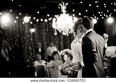 Stunning Couple Dance Under Rich Chandeliers In A Restaurant