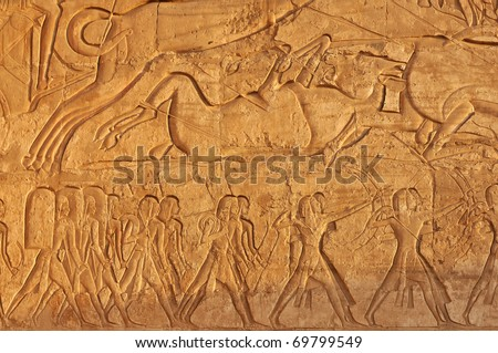 Stunning detail on an ancient egyptian hunting scene showing a bull being killed by spear and arrows with hunters carrying rope; shields; bows; and a war chariot.