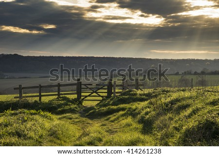 Stunning English countryside landscape over fields at sunset