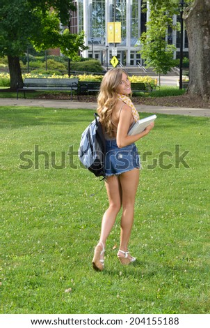 Stunning female college student stands outside with her books - looking over shoulder at viewer as she walks away - heading off to college - stock photo