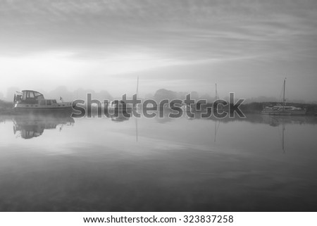 Stunning foggy sunrise over peaceful river landscape in English countryside in black and white - stock photo