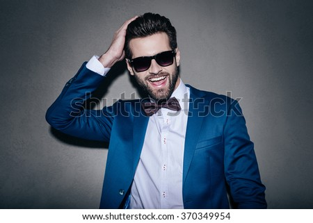 Stunning handsome. Close-up of handsome young cheerful man in suit keeping hand in hair and looking at camera with smile while standing against grey background - stock photo
