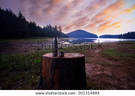 stunning HDR  sunrise at the mountain lake and warm coffee in thermos  - stock photo