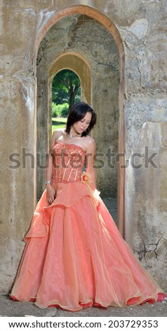 Stunning Hispanic woman in peach colored gown stands in concrete arch