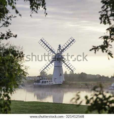 Stunning landscape of windmill and river at sunrise on Summer morning