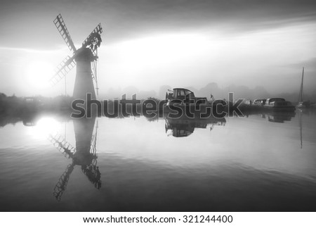 Stunning landscape of windmill and river at sunrise on Summer morning in black and white - stock photo