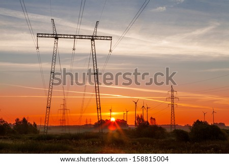 Stunning landscape with wind generators power plant in background and high voltage electricity pylon in foreground at beautiful colorful sunrise