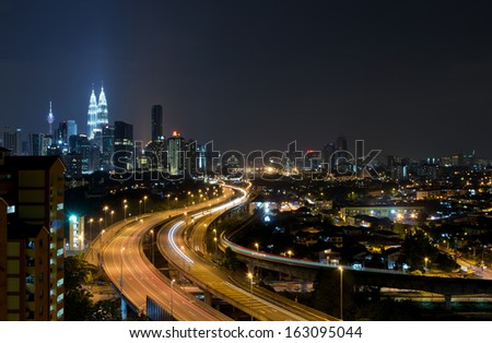Stunning light trail scenery at the busy highway with the view of kuala lumpur city