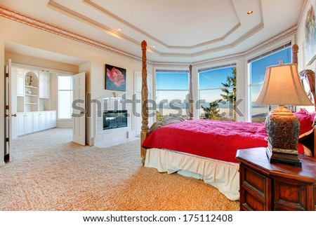 Stunning luxury master bedroom with rich bedroom furniture and amazing angled glass wall overlooking picturesque view - stock photo