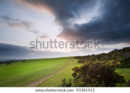Stunning moody sky with beautiful cloud formations and colors over countryside landscape of path leading into distance - stock photo
