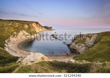 Stunning natural cove coastal landscape at sunset with beautiful sky - stock photo