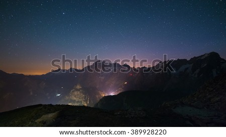 Stunning night view of Mont Blanc peak (4810 m) with breathtaking starry sky above and the glowing cable car up to P. Helbronner. Wide angle view from 3000 m. - stock photo