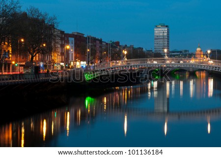 stunning nightscene with Ha'penny bridge and Liffey river, the Custom House landmark at the background (picture taken after sunset) - stock photo