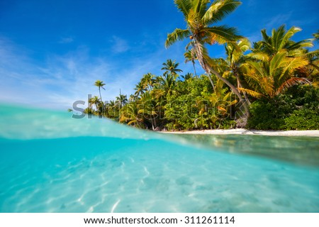 Stunning One Foot island in Aitutaki, tropical island with palm trees, white sand, turquoise ocean water and blue sky at Cook Islands, South Pacific - stock photo