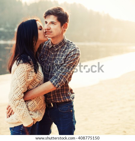 Stunning outdoor lifestyle portrait of young happy kissing fashion couple having fun together in spring on the river in forest - stock photo
