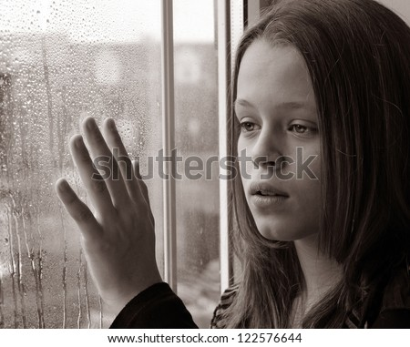 Stunning photo of a young girl gazing through a rainy window with her hand raised in sadness - stock photo
