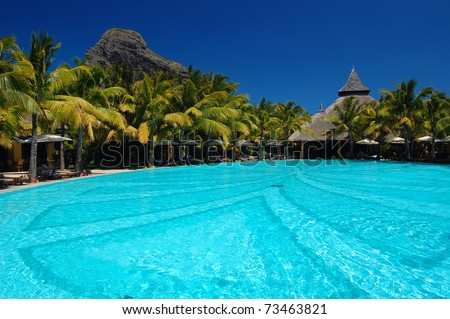 Stunning pool of tropical resort with Le Morne Brabant Mountain on Mauritius Island
