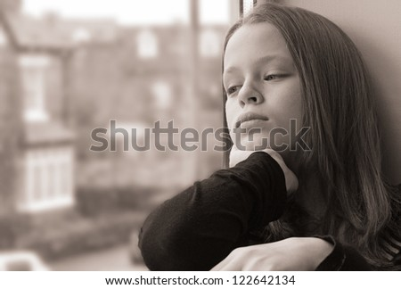 Stunning portrait of a young girl gazing out of the window - stock photo