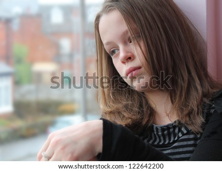 Stunning portrait of a young girl gazing out of the window