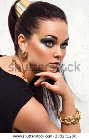 Stunning portrait of young woman with beautiful dark hair and black-gold make-up