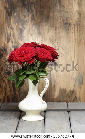 Stunning roses in ceramic vase. Beautiful bouquet on rustic wooden table. Copy space