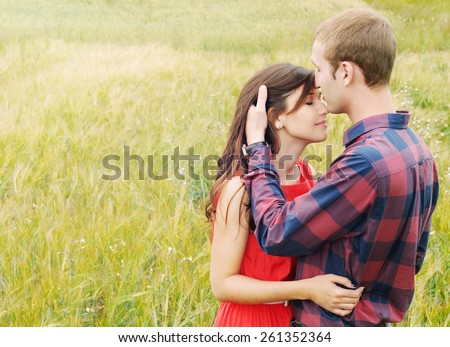 stunning sensual outdoor portrait of young stylish fashion attractive couple in love kissing in summer field - stock photo