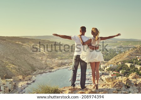 Stunning sensual outdoor portrait of young stylish fashion couple kissing in summer - stock photo