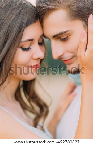 Stunning sensual outdoor portrait of young stylish fashion couple posing in summer field