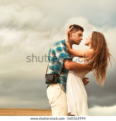 Stunning sensual outdoor portrait of young stylish fashion couple posing in summer in corn field behind rainy clouds and storm.