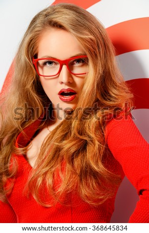 Stunning sensual woman with magnificent blonde hair wearing red dress and elegant red glasses. Beauty, fashion. Optics, eyewear.  - stock photo