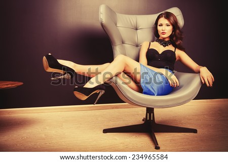 Stunning sexy woman sitting on a chair in a modern interior. Fashion. Interior. - stock photo