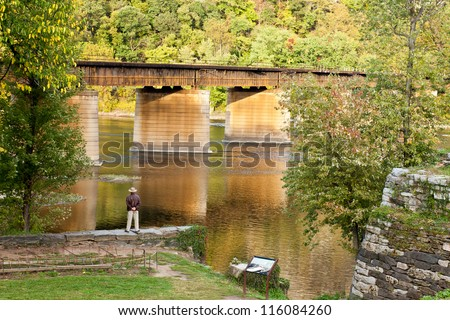 Stunning shot of a man standing on a stone wall overlooking a river next to a bridge - stock photo