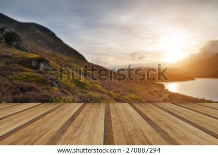 Stunning Summer sunrise over mountain range with lake and beautiful sky with wooden planks floor - stock photo