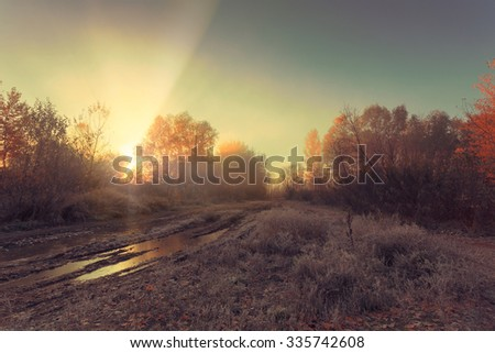 Stunning sun beams light up through thick fog of Autumn Fall frosty landscape. Puddles on the dirt road on foreground. - stock photo