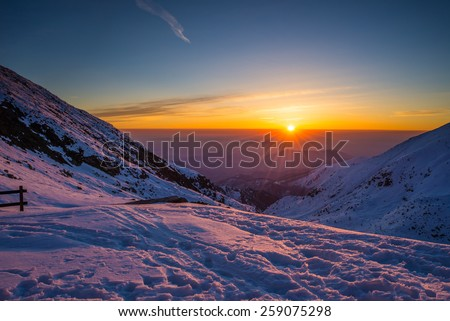 Stunning sunrise at the horizon viewed from high up in the Alps. Majestic panoramic view with snow in the foreground. - stock photo