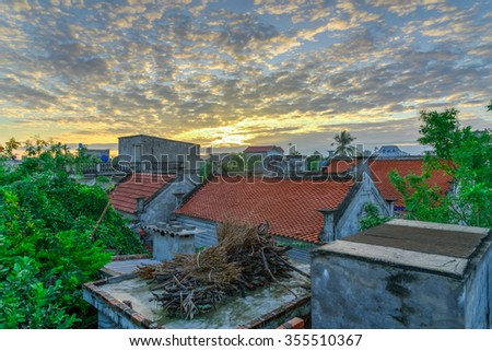 Stunning sunrise countryside landscape in Vietnam with vibrant colors and clouds formations over old houses roof tile pattern. Nature rural landscape background
