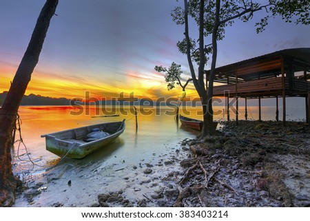 Stunning sunrise over a row of fishing boats on beach in Port Dickson. Vibrant colours.  - stock photo