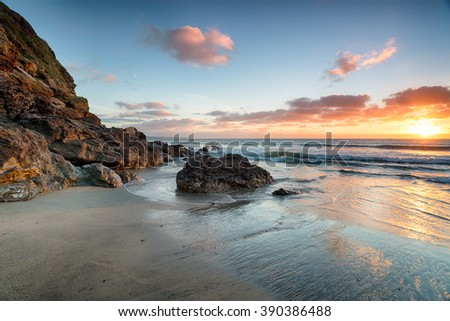 Stunning sunrise over rocks at low tide on the beach at Pentewan on the south coast of Cornwall - stock photo