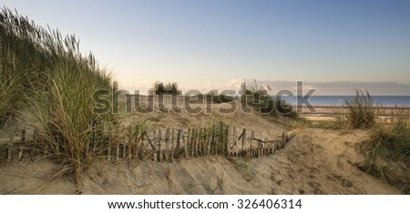 Stunning sunrise over sand dunes system on yellow sand golden beach