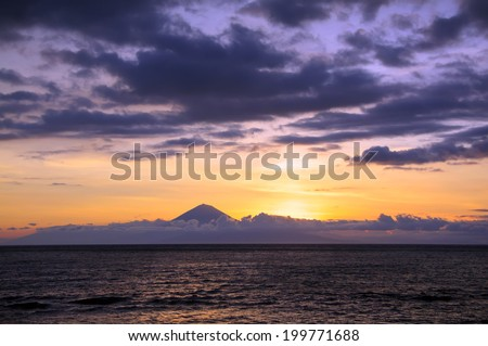 Stunning Sunset of Vibrant Colors on a Seaside with Volcano on a background