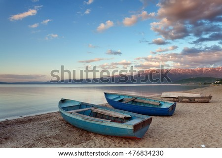 Stunning sunset over Lake Ohrid : wooden boats moored on the beach of Pogradec, Albania