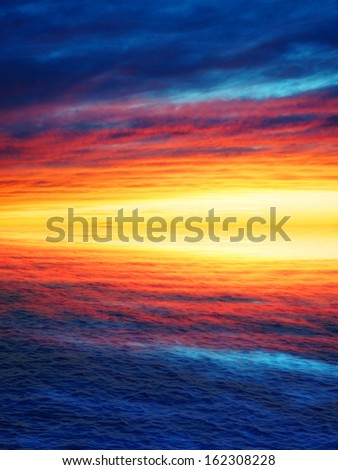 Stunning sunset with very colorful clouds reflected on the waves of the ocean or the sea, nature background - stock photo