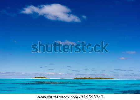 Stunning tropical islands with palm trees, white sand, turquoise ocean water and blue sky at Cook Islands, South Pacific - stock photo
