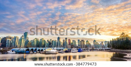 Stunning view of Coal Harbor in British Columbia featuring beautiful downtown buildings, boats,  and reflections on the water