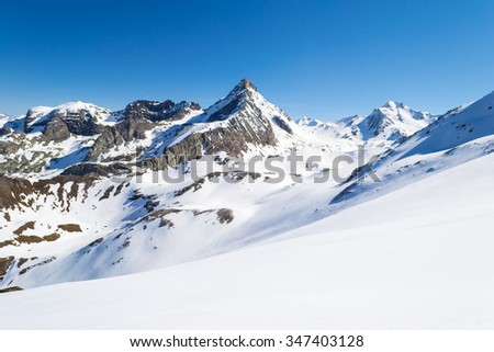 Stunning view of high mountain peaks in the italian alpine arc, in a bright sunny day of winter. Candid snowy slope in the foreground.