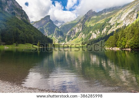 Stunning view  the Alpstein massif on the lake side of of Seealpsee (lake) in summer, Canton of Appenzell, Switzerland - stock photo