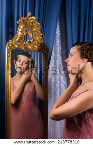 Stunning vintage 1920s woman looking in an antique mirror - stock photo