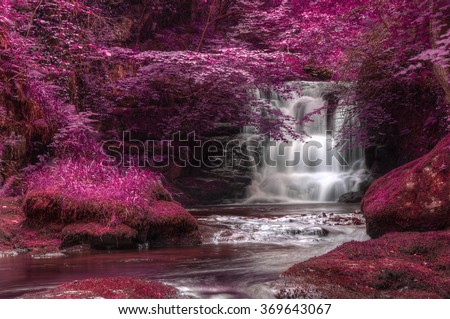Stunning waterfall in alternate surreal colored landscape